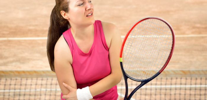 A fenale tennis player holding her elbow in pain