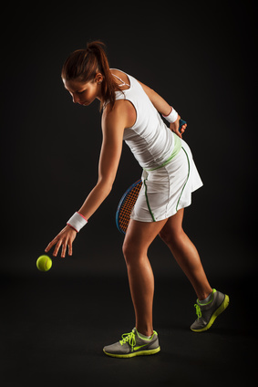 A female tennis player bouncing the ball