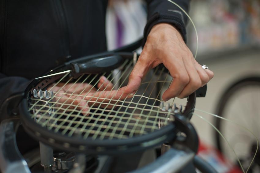 Man restringing a tennis raquet