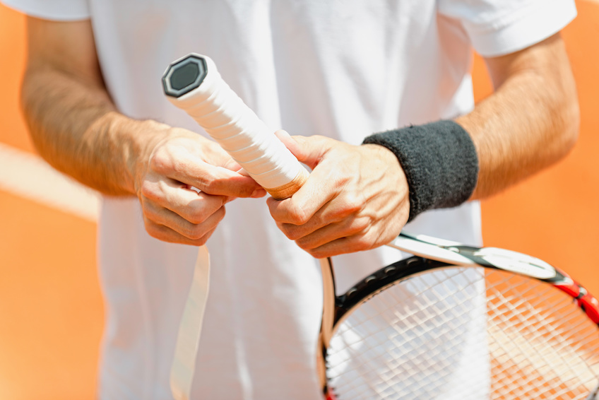 Tennis man putting new grip tape on tennis racquet