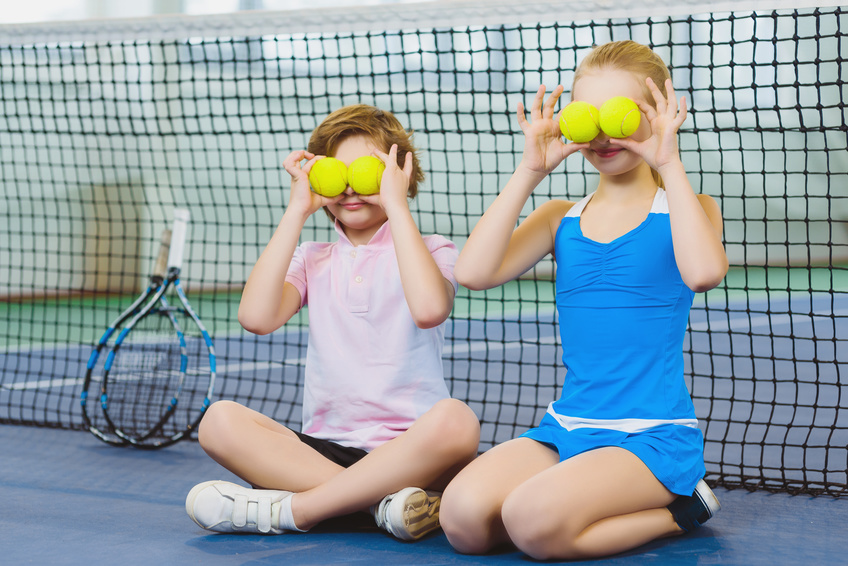 Two children holding choices from our best tennis balls guide over their eyes