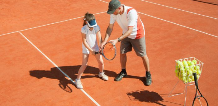 Tennis coach teaching a girl
