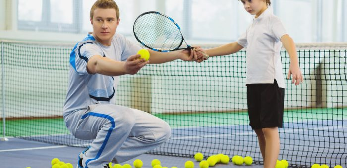 A tennis coach instructing a child