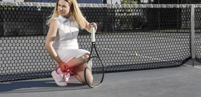 Injured female tennis player, feeling pain in her leg