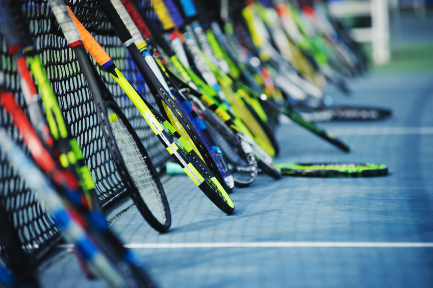 Tennis racquets leaning against the net