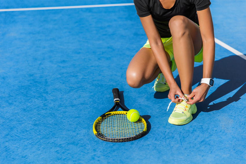 A woman with Plantar Fasciitis putting on tennis shoes