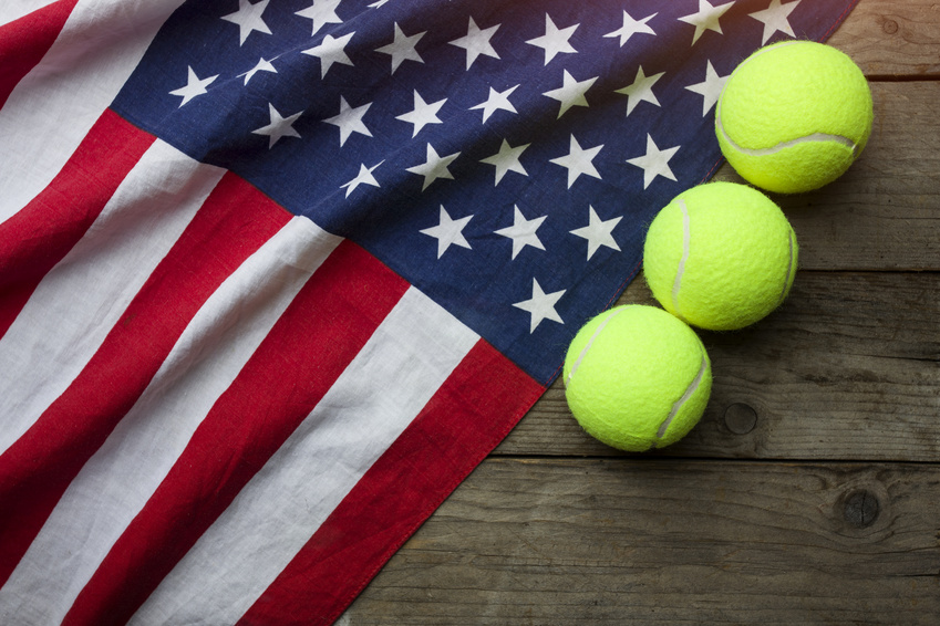 New tennis balls with an American flag on wood table