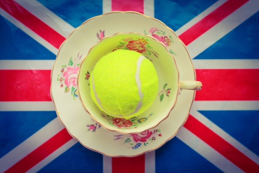 A cup and saucer with a tennis ball inside on top of a union jack flag