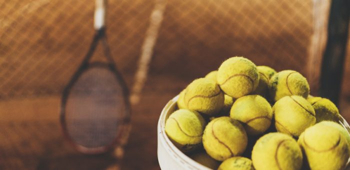 A bucket full of tennis balls with a Donnay tennis racquet in the background