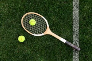 An old tennis racket on a grass court