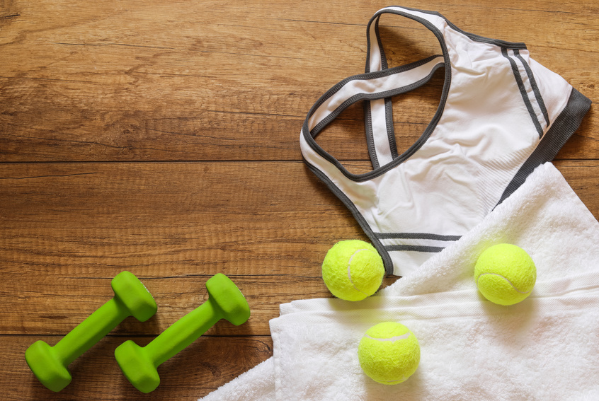 Tennis balls next to dumbbells and gym clothes