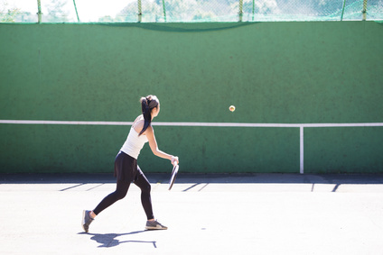A woman playing tennis against a wall