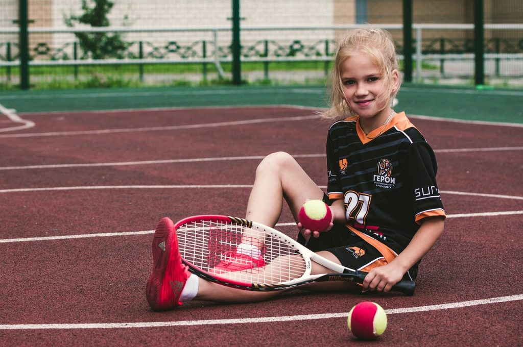 A young girl sat on a tennis court