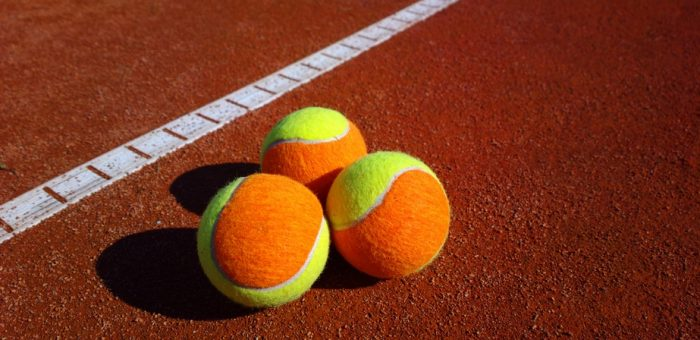 Three coloured tennis balls on a court