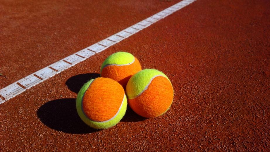 Three coloured tennis balls on a court