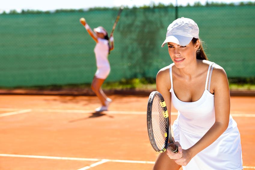 Women playing doubles tennis