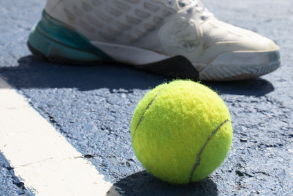 A man with a tennis ball at his feet