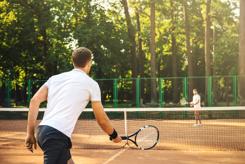 Two men playing singles tennis
