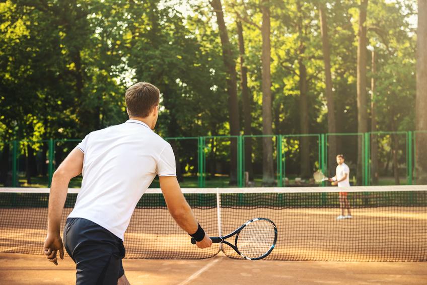 Two men playing singles tennis