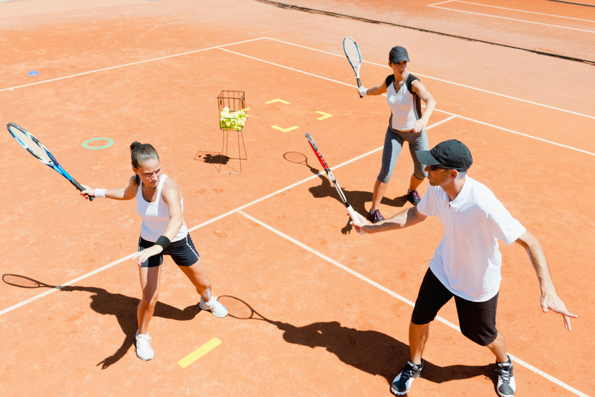 People learning tennis at an academy