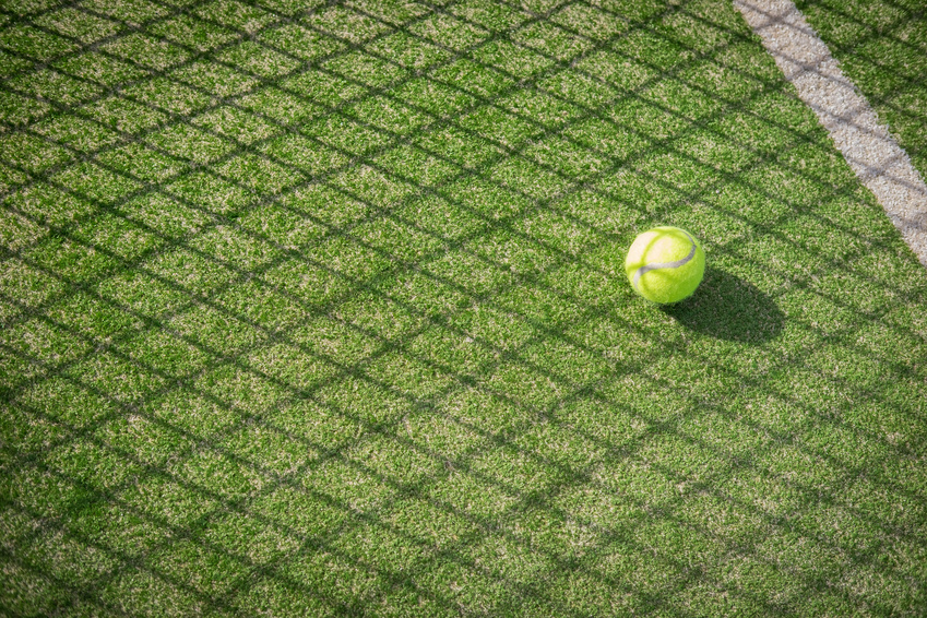 A tennis ball on the floor on a grass court