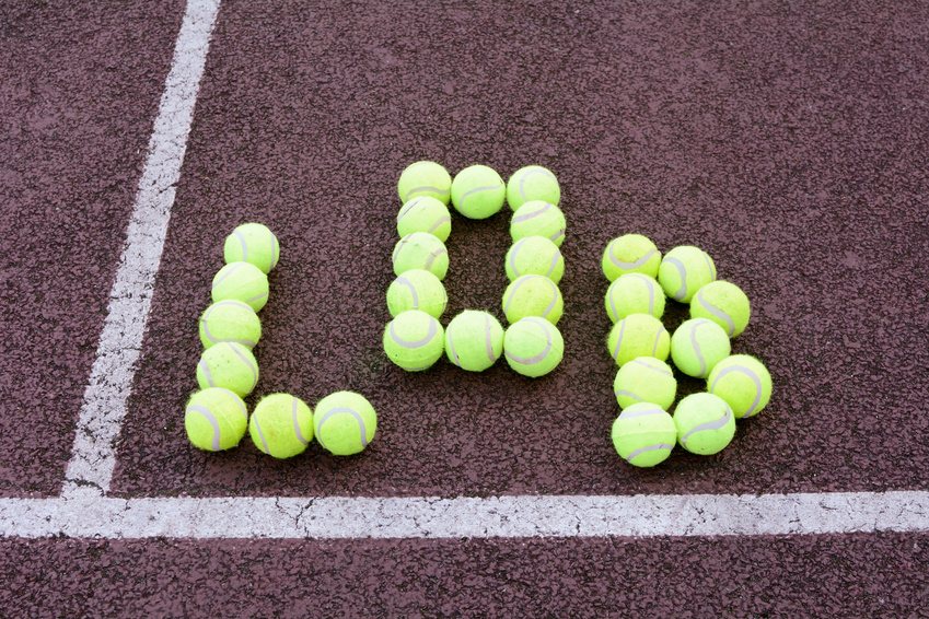"The word ""Lob"" spelt in tennis balls on a court"