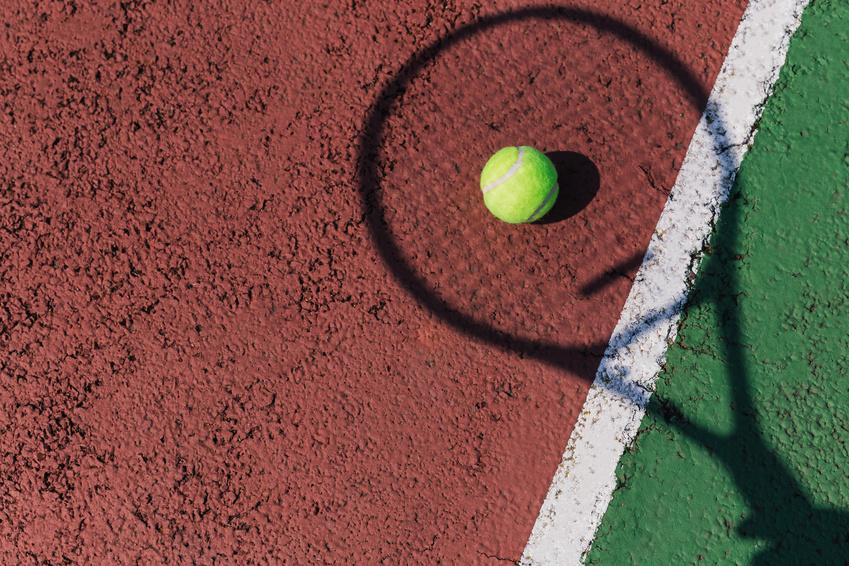A tennis racquet shadow on a court