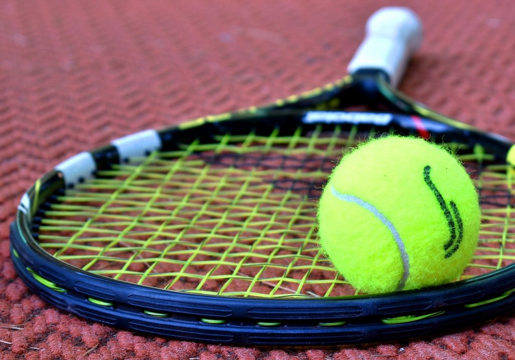A tennis racket lying on the court with a ball on top