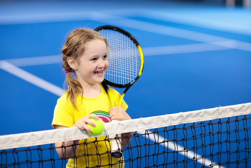A little girl holding a tennis racquet next to the net