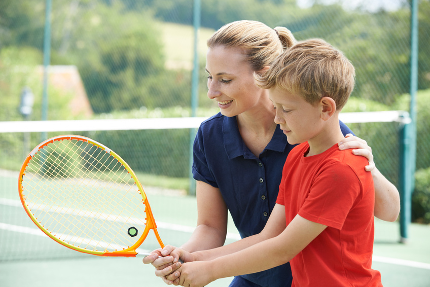 A woman giving tennis lessons to a little boy