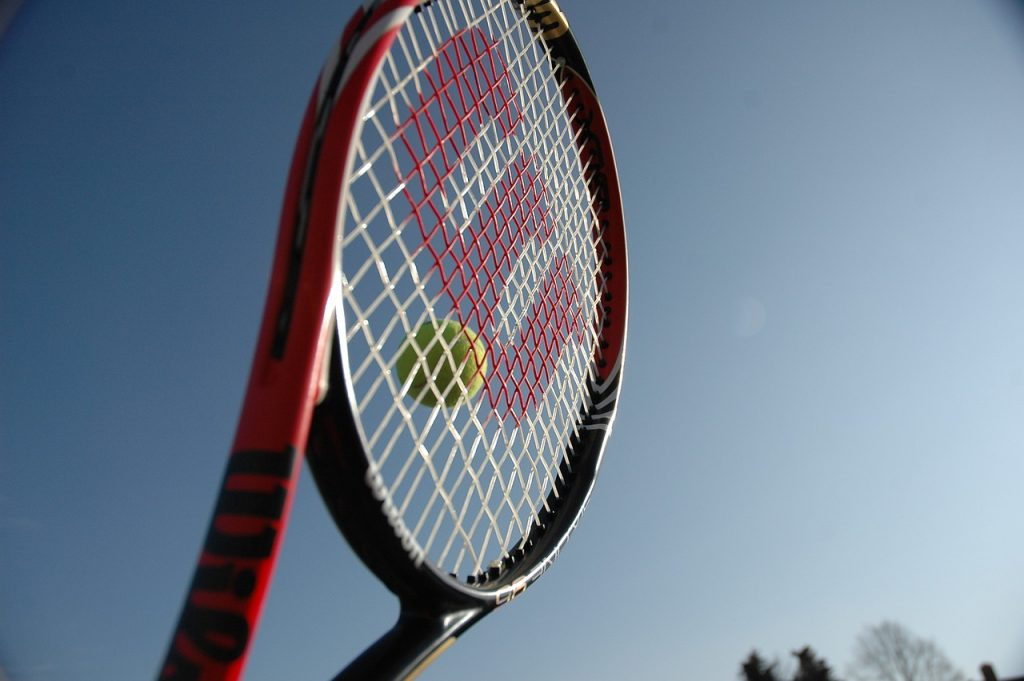 A Wilson tennis racquet hitting a ball
