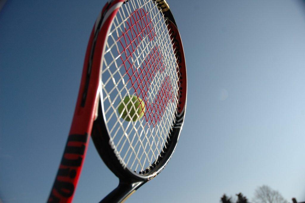 A Wilson tennis racquet hitting a ball