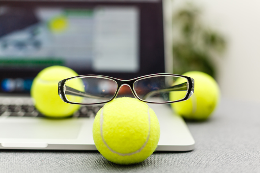 A laptop with tennis statson with balls and glasses