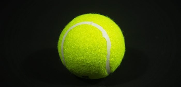 A clean tennis ball on a black background