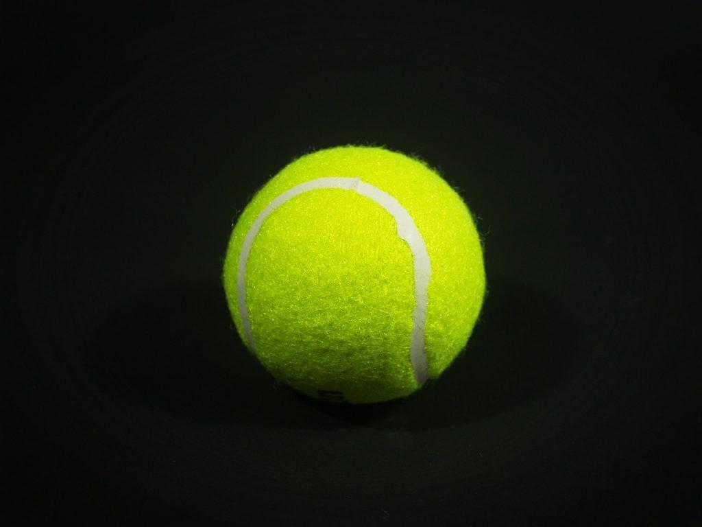 A clean tennis ball on a black background