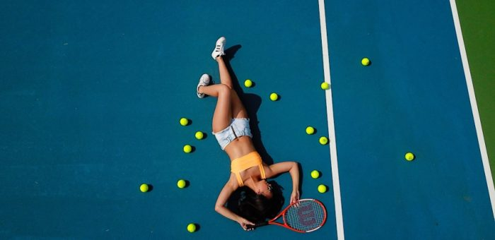 A woman surrounded by tennis balls
