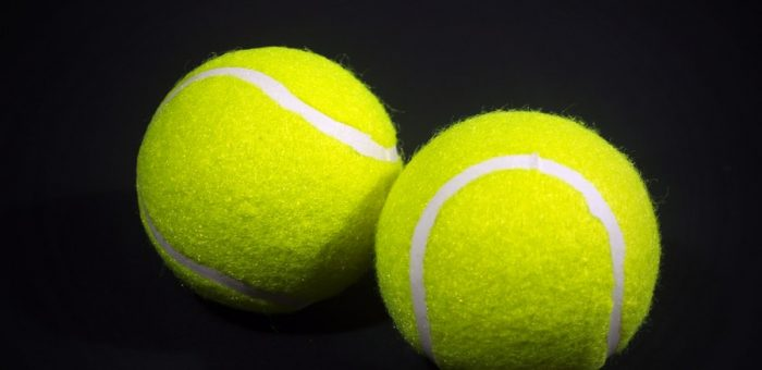 Two tennis balls on black background