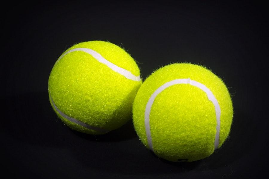 Two tennis balls on black background
