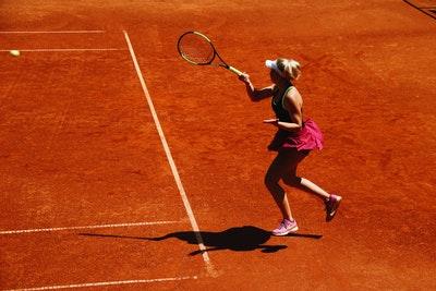 A woman returning a shot from a tennis ball machine