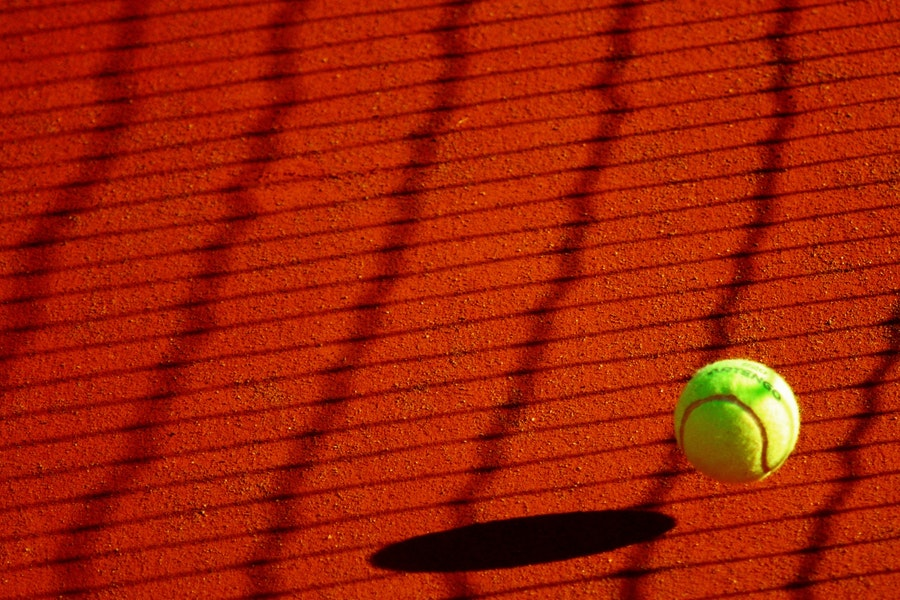 Yellow tennis ball on clay court