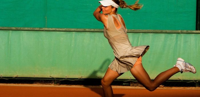 A woman hitting a powerful and accurate tennis shot